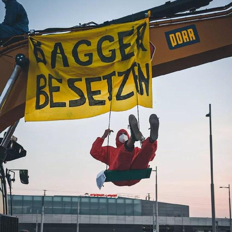 Aktivist schaukelt auf besetztem Bagger, von dem ein Banner hängt